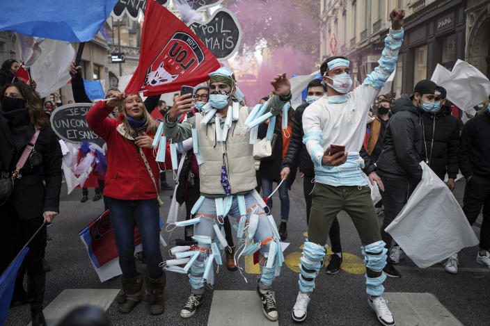 People wearing face masks on their body dance during a demonstration against the closure of the nightclubs, bars, shops and restaurants, in Lyon, central France, Monday, Nov. 23, 2020. France has surpassed 2 million confirmed cases of coronavirus, the fourth-highest total in the world. (AP Photo/Laurent Cipriani)