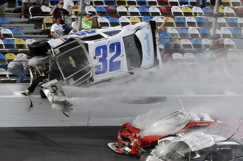 Kyle Larson (32) goes airborne and into the catch fence during a multi-car crash involving Justin Allgaier (31), Brian Scott (2) and others during the final lap of the NASCAR Nationwide Series auto race at Daytona International Speedway, Saturday, Feb. 23, 2013, in Daytona Beach, Fla. Larson's crash sent car parts and other debris flying into the stands injuring spectators. (AP Photo/John Raoux)