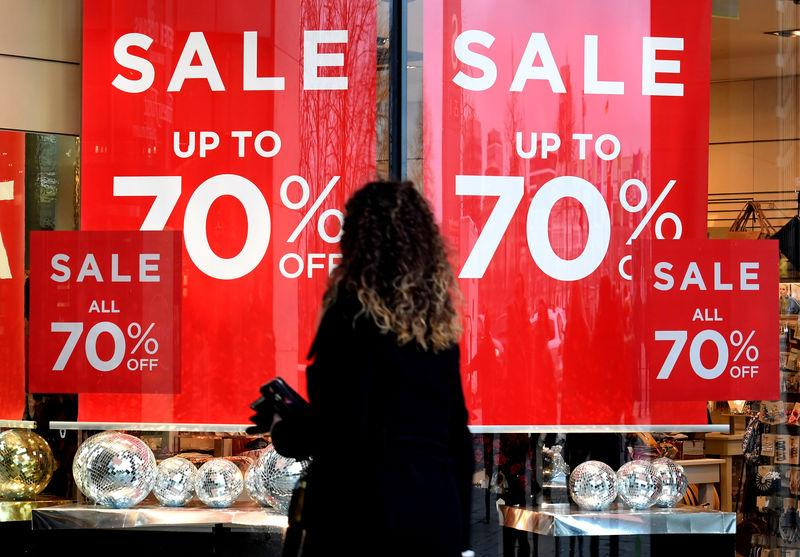 FILE PHOTO: A woman passes sale signs in a shop window in downtown Hamburg