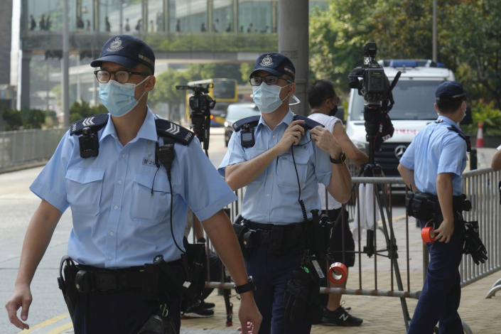"""Police officers stand guard as they wait for Tong Ying-kit's arrival at a court in Hong Kong Tuesday, July 27, 2021. Hong Kong High Court will deliver verdict in the afternoon for the first person charged under Hong Kong's National Security Law. Tong was arrested in July 2020 after driving his motorbike into a group of police officers while carrying a flag bearing the protest slogan """"Liberate Hong Kong."""" He was charged with inciting separatism and terrorism. (AP Photo/Vincent Yu)"""