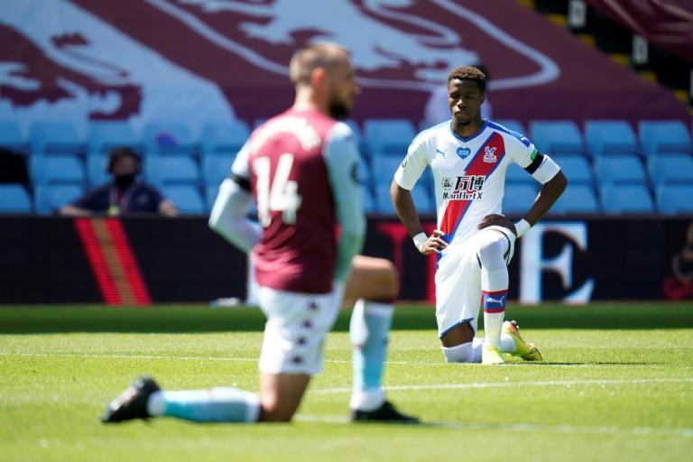 Wilfried Zaha (right)takes a knee prior to Crystal Palace's Premier League match with Aston Villa on Sunday (AFP Photo/Tim Keeton)