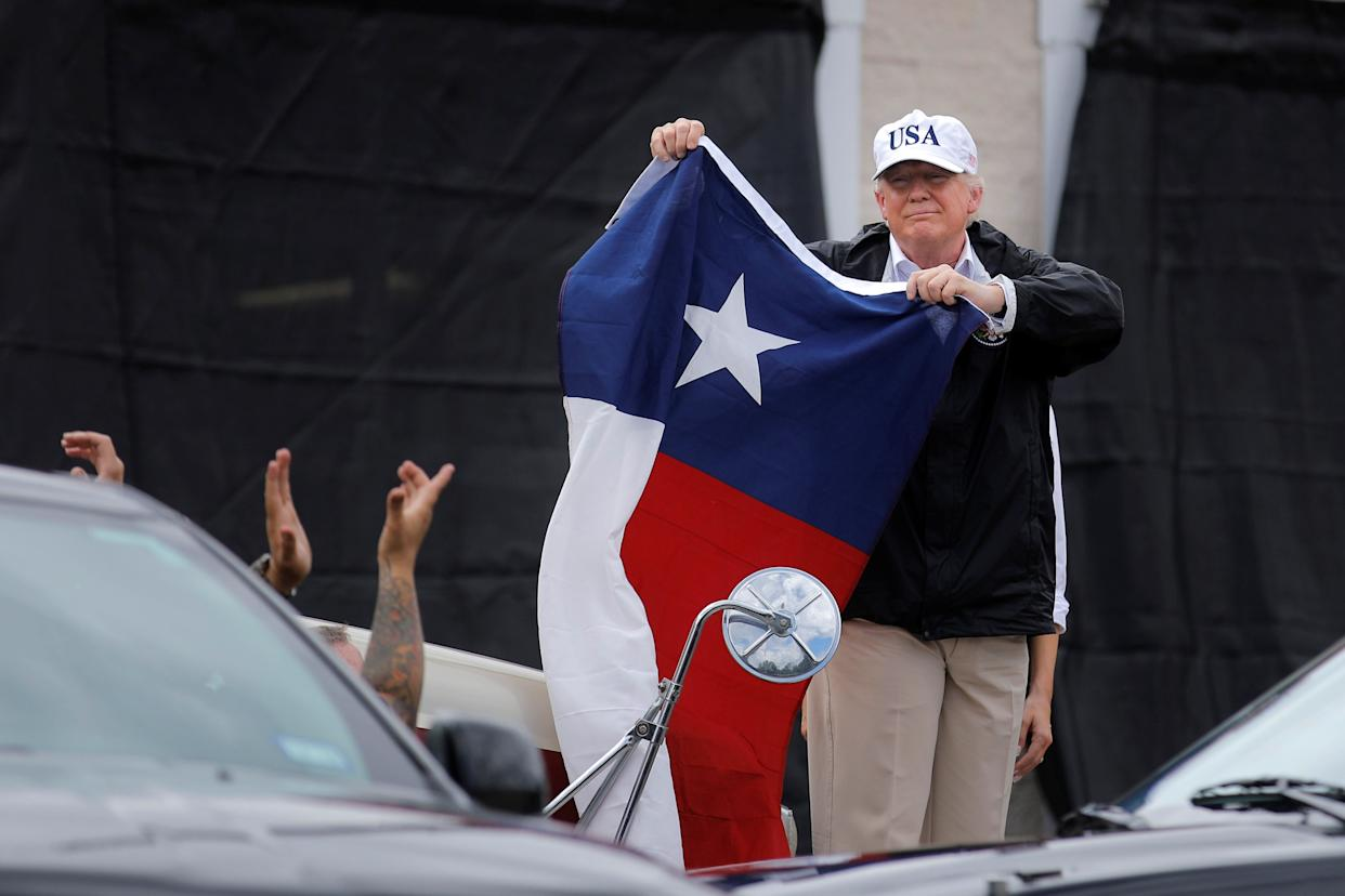 President Donald Trump holds a flag of the state of Texas after receiving a briefing on Tropical Storm Harvey relief efforts at a local fire station in Corpus Christi, Texas.