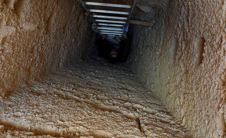 A journalist is seen on the ladder at the entrance to the tombs, during the presentation of a new discovery at Tuna el-Gebel archaeological site in Minya Governorate, Egypt, February 2, 2019. REUTERS/Amr Abdallah Dalsh