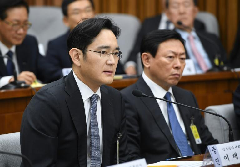 Samsung Group's heir-apparent Lee Jae-Yong (L) answers a question as Lotte Group Chairman Shin Dong-Bin listens during a parliamentary probe into a scandal engulfing President Park Geun-Hye, at the National Assembly in Seoul, on December 6, 2016