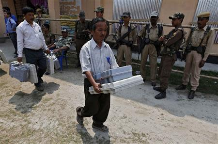 Election officials carry Electronic Voting Machines (EVM) as Indian security personnel stand guard at a distribution centre ahead of general elections in Jorhat district, in the northeastern Indian state of Assam April 6, 2014. REUTERS/Adnan Abidi