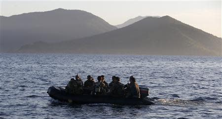 Members of the Philippine marines are transported on a rubber boat from a patrol ship, after a mission at the disputed Second Thomas Shoal, part of the Spratly Islands in the South China Sea, as they return to a naval forces camp in Palawan province, soutwest Philippines March 31, 2014. REUTERS/Erik De Castro