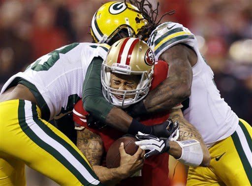 San Francisco 49ers quarterback Colin Kaepernick (7) is tackled by Green Bay Packers free safety M.D. Jennings (43) and outside linebacker Erik Walden (93) during the second quarter of an NFC divisional playoff NFL football game in San Francisco, Saturday, Jan. 12, 2013. (AP Photo/Marcio Jose Sanchez)