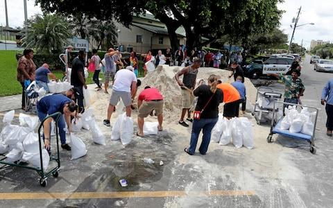 Residents line up at Frost Park in Dania Beach, Fla., and fill up sandbags - Credit: Mike Stocker/South Florida Sun-Sentinel/AP