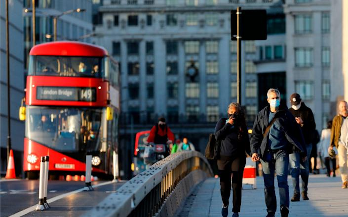 People cross London Bridge as they make their way home in the evening sunshine, in London on September 25, 2020, as new restrictions are introduced to combat the spread of the coronavirus. - Tolga Akmen/AFP