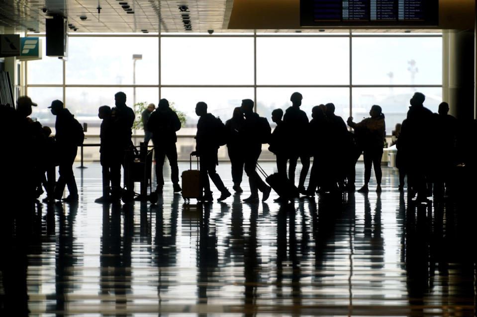 FILE - In this March 17, 2021 file photo, travelers walk through the Salt Lake City International Airport in Salt Lake City. On Friday, June 4, 2021, The Associated Press reported on stories circulating online incorrectly asserting that airlines recently met to discuss the risks and liability of carrying passengers vaccinated against COVID-19. (AP Photo/Rick Bowmer, File)