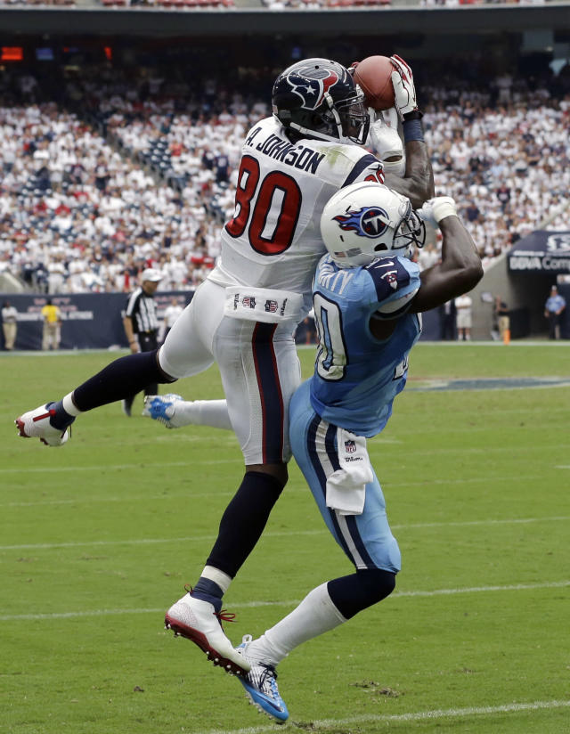 Houston Texans' Andre Johnson (80) catches a pass over Tennessee Titans' Jason McCourty, right, during the fourth quarter of an NFL football game on Sunday, Sept. 15, 2013, in Houston. Johnson was injured on the play. (AP Photo/David J. Phillip)