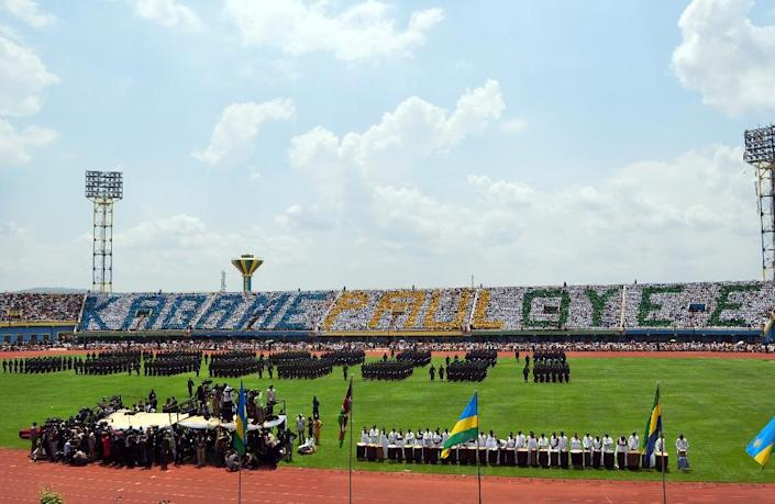 """Rwanda's soldiers parade at the Amahoro stadium as people sit in the stands in a pattern that spelled the words """"Kagame Paul Oye-E"""" during Rwanda's President Paul Kagame swearing-in ceremony in Kigali, on September 6, 2010 (AFP Photo/)"""
