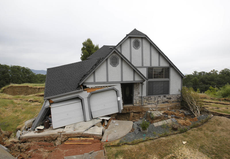 This photo taken Monday, May 6, 2013 shows the wreckage of the Tudor-style dream home of Robin and Scott Spivey who were forced to abandon after the ground gave way causing it to drop 10 feet below the street in Lakeport, Calif. Officials believe that water that has bubbled to the surface is playing a role, in the collapse of the hillside subdivision that has forced the evacuation of 10 homes and the notice of imminent evacuation of another 10 in this upscale subdivision.(AP Photo/Rich Pedroncelli)