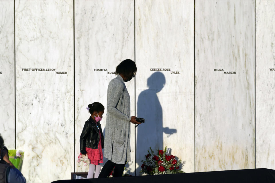 Family of Flight 93 first officer Leroy Homer walk along the Wall of Names at the Flight 93 National Memorial in Shanksville, Pa. before a Service of Remembrance Saturday, Sept. 11, 2021, as the nation marks the 20th anniversary of the Sept. 11, 2001 attacks. (AP Photo/Gene J. Puskar)
