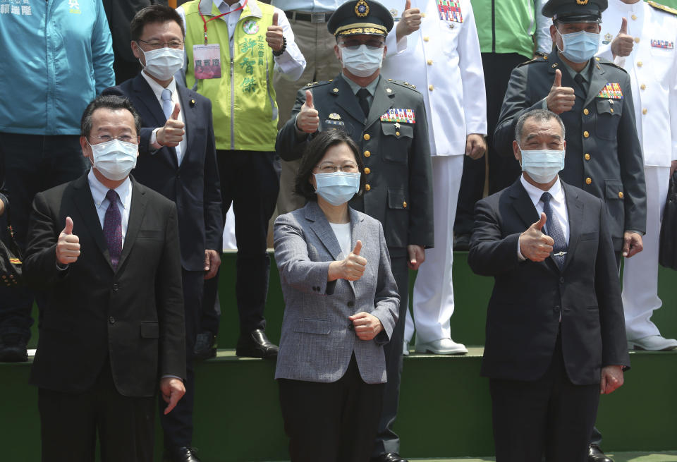 Taiwan's President Tsai Ing-wen, center, cheers with officers during a launch ceremony for its first indigenous amphibious transport dock in Kaohsiung, southern Taiwan, Tuesday, April 13, 2021. (AP Photo/Chiang Ying-ying)