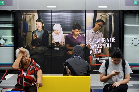FILE PHOTO Commuters sit in front of an advertisement discouraging the dissemination of fake news, at a train station in Kuala Lumpur, Malaysia March 28, 2018. REUTERS/Stringer/File Photo