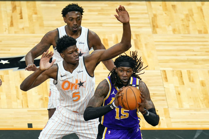 Los Angeles Lakers center Montrezl Harrell (15) passes the ball as his path to the basket is blocked by Orlando Magic center Mo Bamba (5) and forward Robert Franks, back left, during the first half of an NBA basketball game, Monday, April 26, 2021, in Orlando, Fla. (AP Photo/John Raoux)