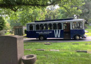 A trolley waits during a stop on a tour of jazz and vaudeville greats at Woodlawn Cemetery in the Bronx on June 27, 2021. The tour takes visitors to the gravesites of Irving Berlin, Duke Ellington, George M. Cohan, W.C. Handy, King Oliver and other musicians. (AP Photo/Julia Rubin)