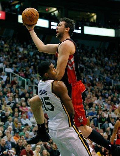 Toronto Raptors forward Andrea Bargnani, top, of Italy, draws a charging foul on Utah Jazz forward Derrick Favors, left, during the first half of their NBA basketball game in Salt Lake City on Wednesday, Jan. 25, 2012. (AP Photo/Steve C. Wilson)