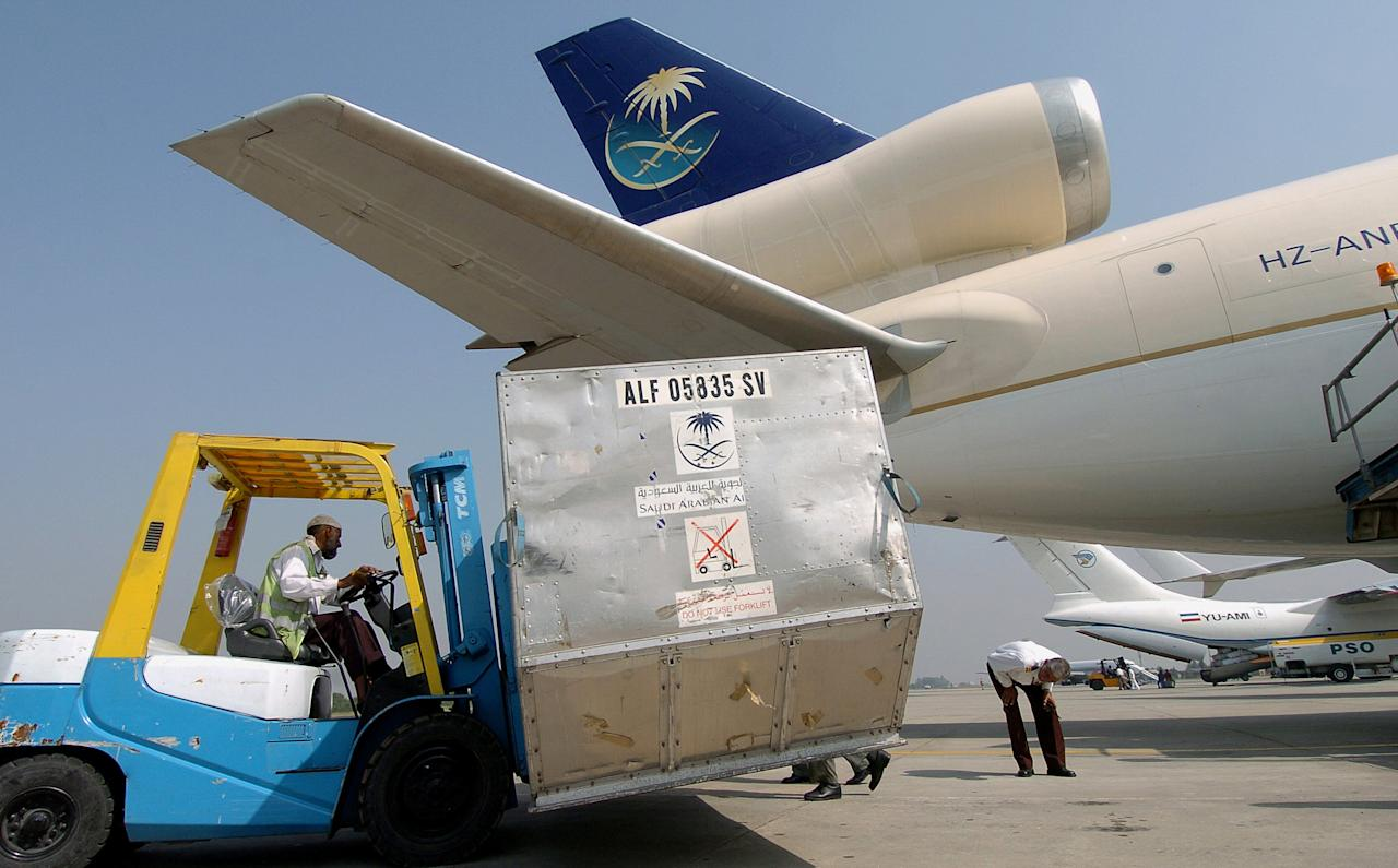 Pakistani workers off-load relief goods from a Saudia Arabian cargo plane destined for the worst earthquake hit areas of Pakistan administered Kashmir from Chaklala air base in Rawalpindi, 17 October 2005.  Helicopters resumed relief operations to stranded and desperate earthquake survivors in the snow-dusted mountains of Pakistani Kashmir after a full day lost to bad weather.   AFP PHOTO/ ASIF HASSAN