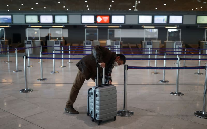 A passenger waits for check-in in the departures area of the Terminal 2E at Charles-de-Gaulle airport in Roissy
