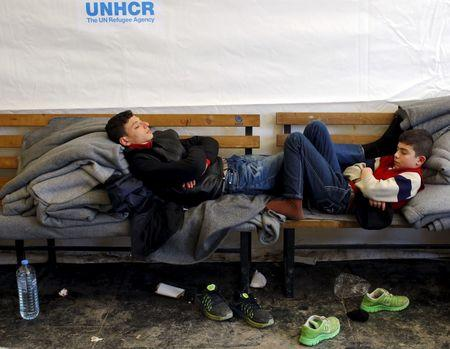 A migrant child sleeps while waiting for transport to Serbia at a transit camp near Gevgelija