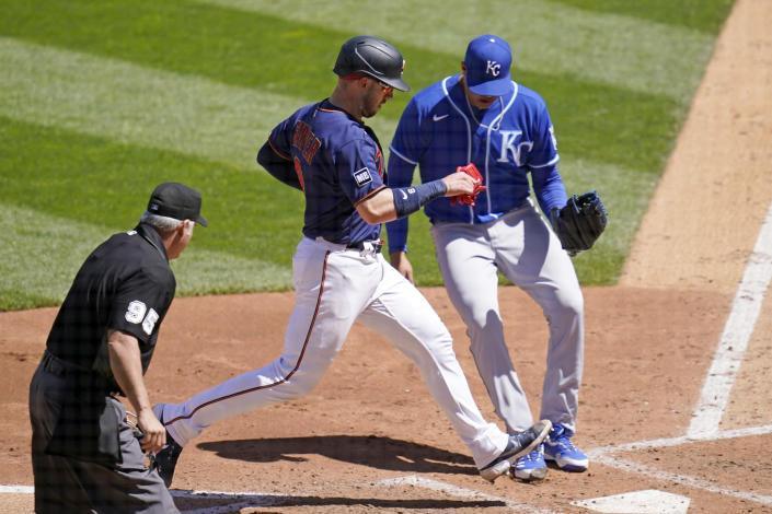 Minnesota Twins' Mitch Garver, center left, scores on a passed ball off Kansas City Royals pitcher Carlos Hernandez, right, in the fourth inning of a baseball game, Saturday, May 29, 2021, in Minneapolis. (AP Photo/Jim Mone)