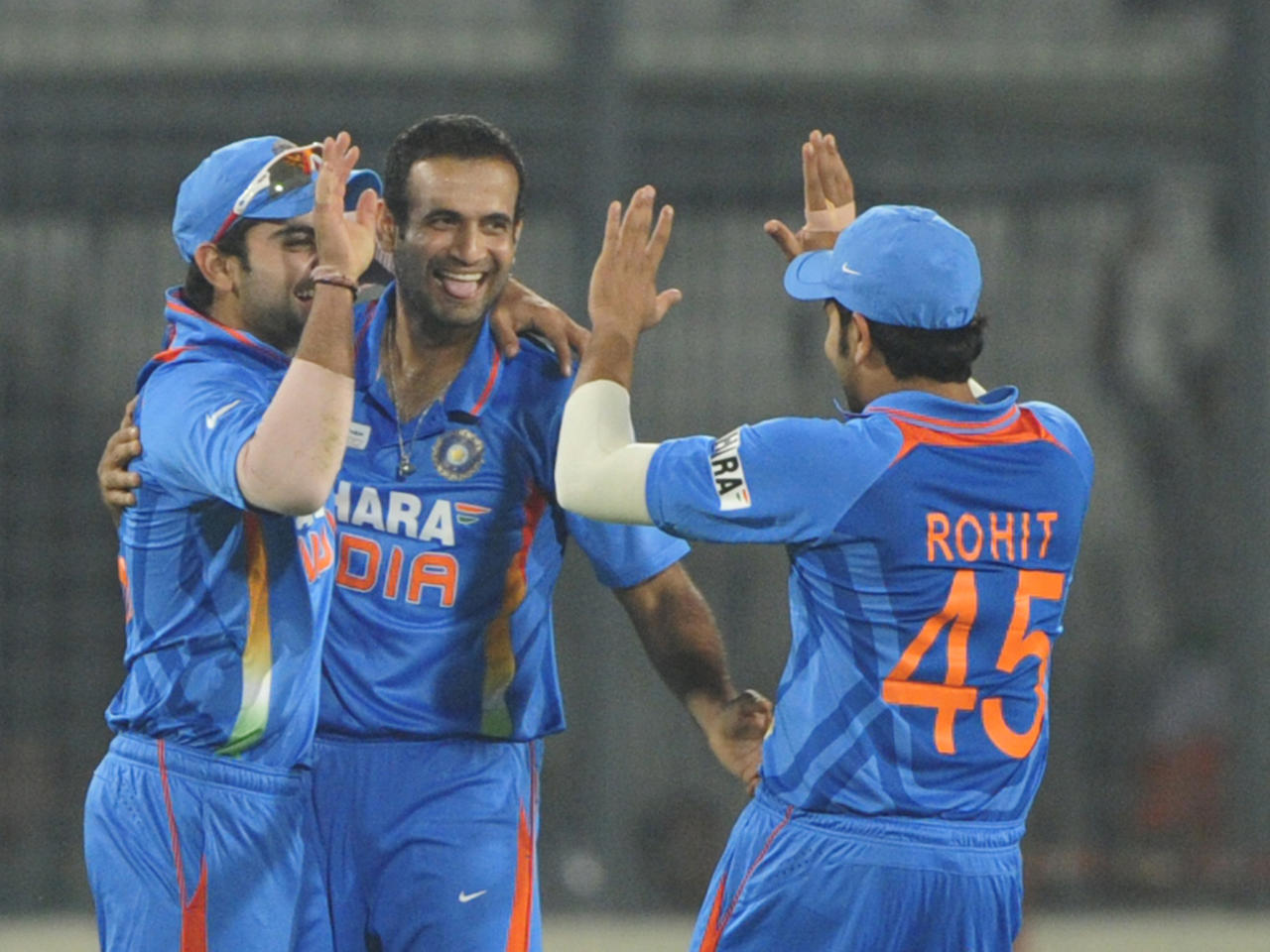 Indian cricketer Virat Kohli (L), Irfan Pathan (C) and Rohit Sharma (R) celebrate the dismissal of Sri Lankan batsman Tillakaratne Dilshan during the one day international (ODI) Asia Cup cricket match between India and Sri Lanka at The Sher-e-Bangla National Cricket Stadium in Dhaka on March 13, 2012.