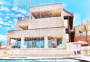 Looking through the poolside waterfall at the modern, 3-story clubhouse with rooftop patio.