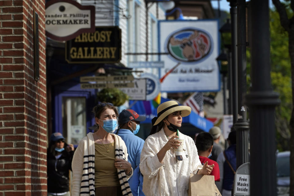 Visitors walk on a busy sidewalk, Saturday, May 15, 2021, in Bar Harbor, Maine. Gov. Janet Mills is is eliminating most outdoor distancing requirements imposed during the COVID-19 pandemic as the tourism season begins to kick into gear. (AP Photo/Robert F. Bukaty)