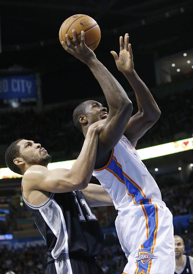 Oklahoma City Thunder forward Serge Ibaka, right, is fouled by San Antonio Spurs forward Jeff Ayres (11) as he shoots in the second quarter of an NBA basketball game in Oklahoma City, Wednesday, Nov. 27, 2013. (AP Photo/Sue Ogrocki)