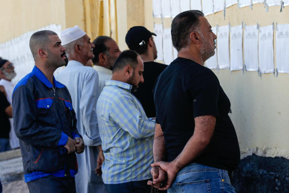 Voters look for their names on a list during parliamentary elections at a polling station in Najaf, Iraq, Sunday, Oct. 10, 2021. Iraq closed its airspace and land border crossings on Sunday as voters headed to the polls to elect a parliament that many hope will deliver much needed reforms after decades of conflict and mismanagement. (AP Photo/Anmar Khalil)