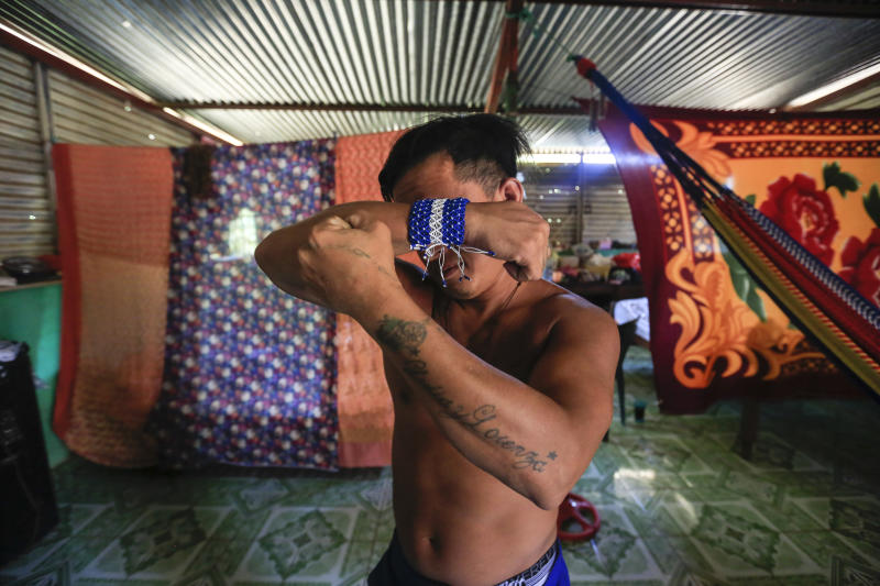 Prisoner Franklin Perez, 29, strikes a pose showing off his tattoos, one dedicated to his mother, the other to his deceased daughter, in his home after he was released to house arrest, in Managua, Nicaragua, Friday, April 5, 2019. Perez is among the 50 people released Friday who had been jailed for protesting against President Daniel Ortega's government. However charges were not dropped against the demonstrators. Instead they were for the most part transferred to a form of house arrest, short of the unrestricted freedom that the opposition has demanded. (AP Photo/Alfredo Zuniga)