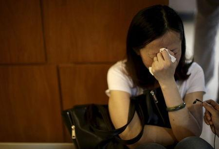 A family member of passengers on the ship which sank at the Jianli section of Yangtze River, in Hubei province, cries outside a closed office of Xiehe Travel in Shanghai, China, June 2, 2015. REUTERS/Stringer