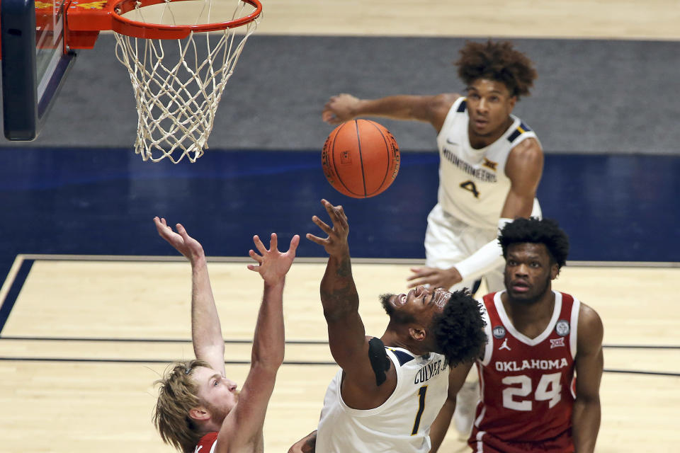West Virginia forward Derek Culver (1) shoots as Oklahoma forward Brady Manek (35) and guard Elijah Harkless (24) defends during the first half of an NCAA college basketball game Saturday, Feb. 13, 2021, in Morgantown, W.Va. (AP Photo/Kathleen Batten)