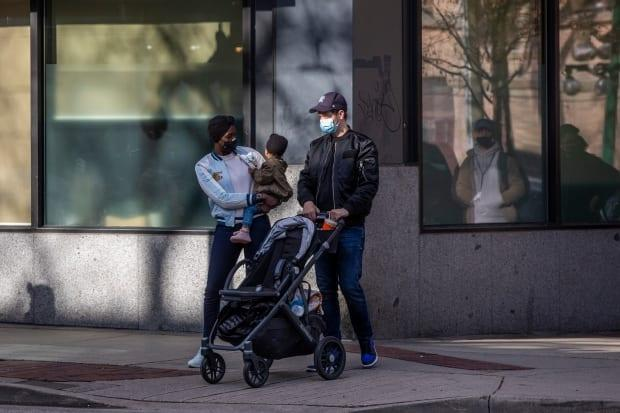 A family waits to cross a street in Vancouver on Monday.