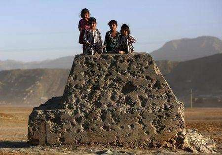 Afghan children sit on a bullet-riddled concrete block in Kabul