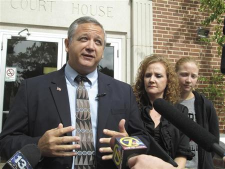 Suspended Liberty County Sheriff Nick Finch, with his wife Angela (C) and daughter Amber (R), talks with reporters on the steps of the courthouse after his acquittal on charges of official misconduct and falsifying official documents in Tallahassee, Florida October 31, 2013. REUTERS/Bill Cotterell