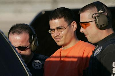 In this Jan. 5, 2006 file photo, Jose Padilla, center, is escorted to a waiting police vehicle by federal marshals near downtown Miami. (AP Photo/J. Pat Carter, File)