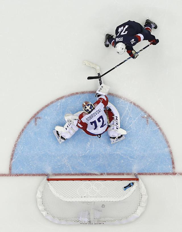 USA forward T.J. Oshie scores a goal on Russia goaltender Sergei Bobrovski during a shootout in a men's ice hockey game at the 2014 Winter Olympics, Saturday, Feb. 15, 2014, in Sochi, Russia. (AP Photo/Julio Cortez )