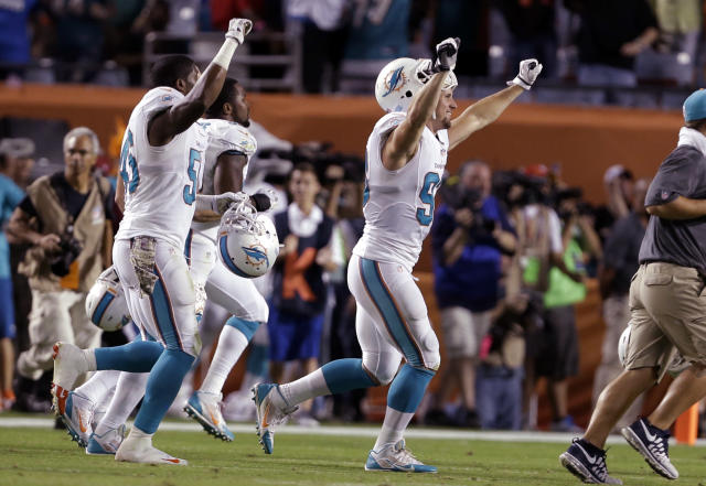 Miami Dolphins outside linebacker Jason Trusnik, right, runs onto the field with his teammates after the Dolphins defeated the San Diego Chargers 20-16 in an NFL football game, Sunday, Nov. 17, 2013, in Miami Gardens, Fla. (AP Photo/Lynne Sladky)