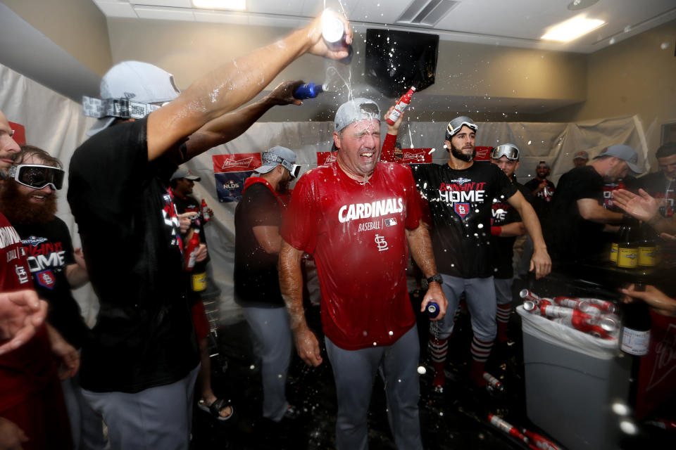 St. Louis Cardinals bullpen coach Bryan Eversgerd, center, is doused with beer as players celebrate in the clubhouse after the Cardinals beat the Atlanta Braves 13-1 in Game 5 of their National League Division Series baseball game Wednesday, Oct. 9, 2019, in Atlanta. (AP Photo/John Bazemore)