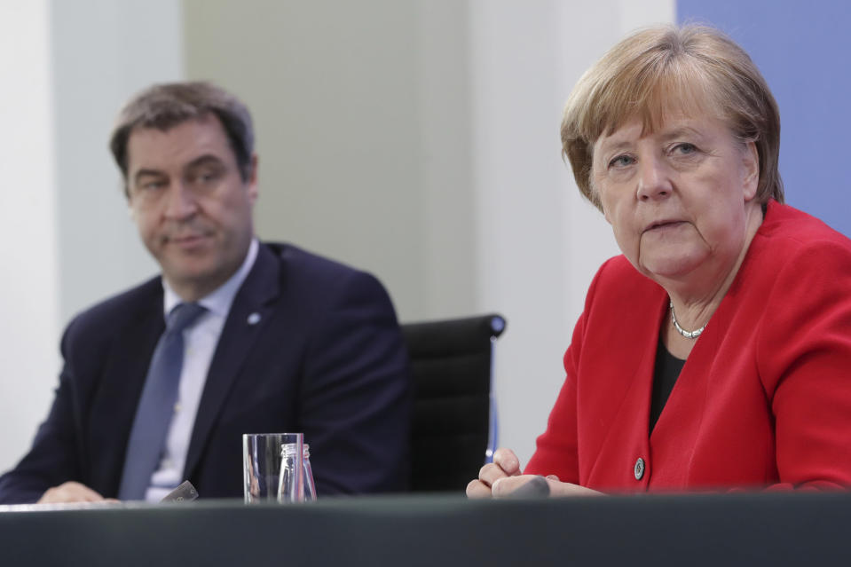 """FILE - In this Wednesday, May 6, 2020 file photo Bavarian Governor Markus Soeder and German Chancellor Angela Merkel address the media during a joint press conference in Berlin, Germany. Armin Laschet, a governor who also leads Merkel's party, called this week for a vaguely defined 2-3 week """"bridge lockdown"""" to control infections while Germany steps up a so-far slow vaccination campaign. German Chancellor Angela Merkel has thrown her weight behind calls for a 'short, uniform lockdown'. (AP Photo/Michael Sohn, file, pool)"""