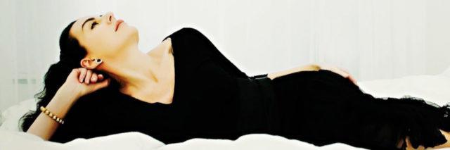 woman in a black dress lying on a white bed against a white background