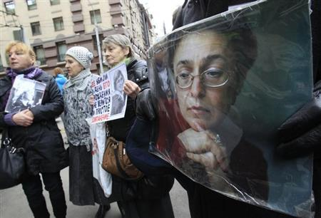 People hold portraits of slain journalist Politkovskaya on the sixth anniversary of her death, next to her block of flats in central Moscow