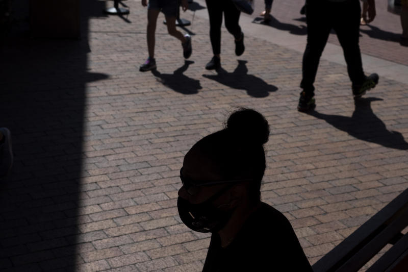 """A shopper wearing a face mask sits in the shade at the Citadel Outlets in Commerce, Calif., Thursday, July 2, 2020. California Gov. Gavin Newsom on Thursday urged Californians to turn to their """"better angels"""" and use common sense over the holiday weekend by wearing a mask and skipping traditional gatherings with family and friends. (AP Photo/Jae C. Hong)"""