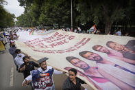 Indian Youth Congress members carry a giant banner during a protest held to mark Indian Prime Minister Narendra Modi's birthday in New Delhi, India, Friday, Sept.17, 2021. Youth members of main opposition Congress party clashed with police during a street protest Friday demanding jobs as the country's economy recovered from the impact of the COVID-19 pandemic that triggered massive unemployment in the country. The march took place as supporters of Prime Minister Narendra Modi celebrated his birthday as he turned 71 on Friday. (AP Photo/Manish Swarup)