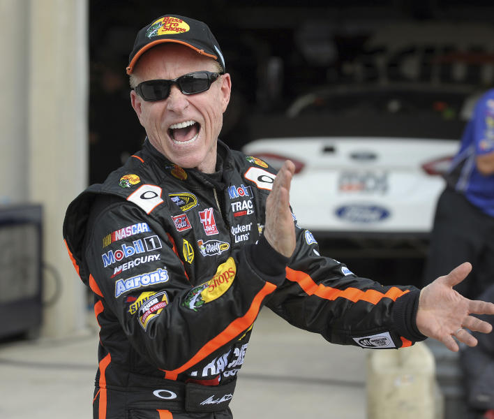Driver Mark Marin laughs as he walks through the garage area during a practice session for Sunday's NASCAR Sprint Cup series auto race at Atlanta Motor Speedway in Hampton, Ga., Friday, Aug. 30, 2013. (AP Photo/Dave Tulis)