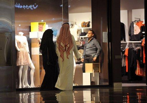 A Saudi man and woman walk past a clothes shop at a local mall in Riyadh on August 18, 2012