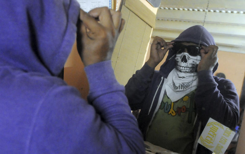 "In this July 29, 2012 photo, a masked artist who calls himself the Urban Maeztro and prefers to remain anonymous for security reasons, adjusts his mask and sunglasses in his studio before going out to paste his ""interventions"" on street walls in Tegucigalpa, Honduras.  The 26-year-old graphic artist left his day job at an advertising agency to create pieces to exhibit in public places that encourage Hondurans think about how violent their country has become.  (AP Photo/Fernando Antonio)"
